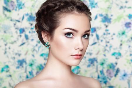 花の背景に若い美しい女性の肖像画。ファッション写真。宝石と髪型。完璧なメイク 写真素材