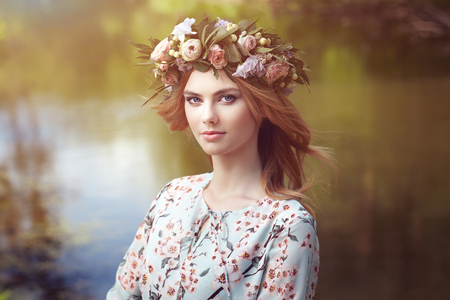 flower head: Beautiful blonde woman with flower wreath on her head. Beauty girl with flowers hairstyle. Girl in a summer forest. Fashion photo