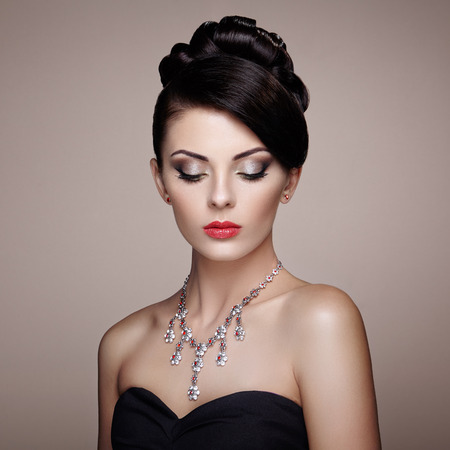 ladylike: Fashion portrait of young beautiful woman with jewelry. Brunette girl. Perfect make-up.  Beauty style woman with diamond accessories Stock Photo