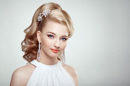 Fashion Portrait der jungen schönen Frau mit Schmuck und elegante Frisur. Blonde Mädchen mit langen gewellten Haaren. Perfekte Make-up. Beauty-Stil Frau mit Diamant-Zubehör Standard-Bild