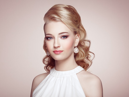 forearms: Fashion portrait of young beautiful woman with jewelry and elegant hairstyle. Blonde girl with long wavy hair. Perfect make-up.  Beauty style woman with diamond accessories Stock Photo
