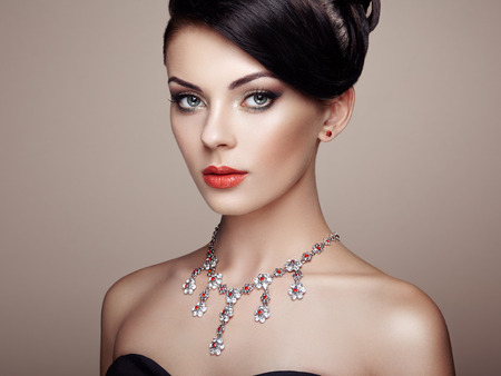 Fashion portrait of young beautiful woman with jewelry. Brunette girl. Perfect make-up.  Beauty style woman with diamond accessories Stock Photo