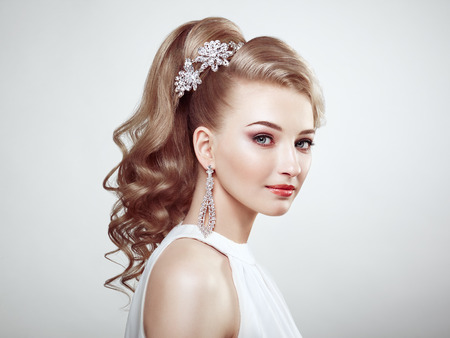 elegant girl: Fashion portrait of young beautiful woman with jewelry and elegant hairstyle. Blonde girl with long wavy hair. Perfect make-up.  Beauty style woman with diamond accessories Stock Photo