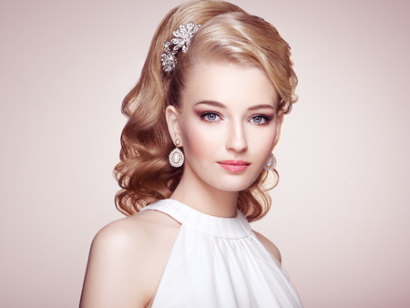 Fashion portrait of young beautiful woman with jewelry and elegant hairstyle. Blonde girl with long wavy hair. Perfect make-up.  Beauty style woman with diamond accessories Imagens