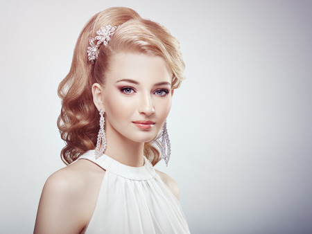 hair and beauty: Fashion portrait of young beautiful woman with jewelry and elegant hairstyle. Blonde girl with long wavy hair. Perfect make-up.  Beauty style woman with diamond accessories Stock Photo