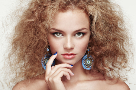 Fashion portrait of young beautiful woman with jewelry and elegant hairstyle. Redhead girl with long curly hair. Perfect make-up Foto de archivo