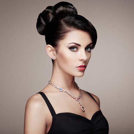 mujeres fashion: Retrato de la mujer hermosa joven con la joyería y el peinado elegante. Chica morena. Maquillaje perfecto. Mujer del estilo de la belleza con los accesorios del diamante
