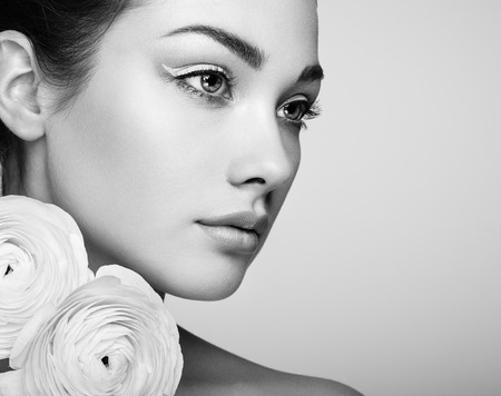 Portrait of beautiful young woman with flowers. Brunette woman with luxury makeup. Perfect skin. Eyelashes. Cosmetic eyeshadow. Black and White Reklamní fotografie