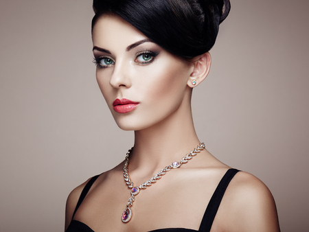 Fashion portrait of young beautiful woman with jewelry and elegant hairstyle. Brunette girl. Perfect make-up.  Beauty style woman with diamond accessories Stock Photo
