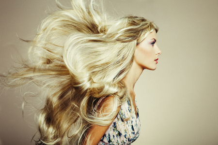 Photo of beautiful woman with magnificent hair. Blonde girl with long and shiny wavy hair . Beautiful model with curly hairstyle Stock Photo