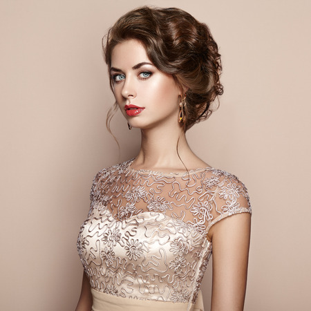 Fashion portrait of beautiful woman in elegant dress. Girl with elegant hairstyle and jewelry 스톡 콘텐츠