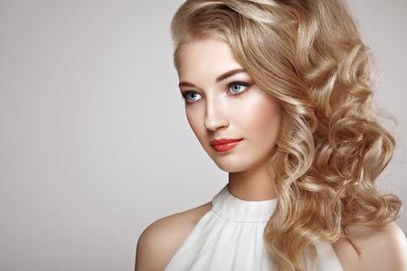 Retrato de la mujer hermosa joven con la joyería y el peinado elegante. chica rubia con el pelo largo y ondulado. Maquillaje perfecto. Mujer del estilo de la belleza con los accesorios del diamante