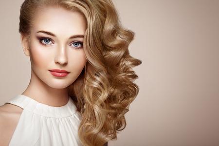 Fashion portret van jonge mooie vrouw met juwelen en elegante kapsel. Blond meisje met lang golvend haar. Perfecte make-up. Schoonheid stijl vrouw met diamant accessoires