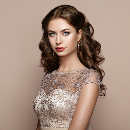 Fashion portrait of beautiful woman in elegant dress. Girl with elegant hairstyle and jewelry Standard-Bild