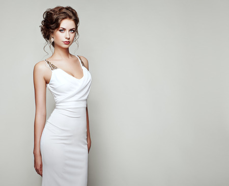 Fashion portrait of beautiful woman in elegant white dress. Girl with elegant hairstyle and jewelry Stok Fotoğraf - 64431543