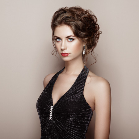 Fashion portrait of beautiful woman in elegant dress. Girl with elegant hairstyle and jewelry Stok Fotoğraf