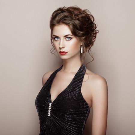 Retrato de la mujer hermosa en vestido elegante. Chica con el peinado elegante y joyas