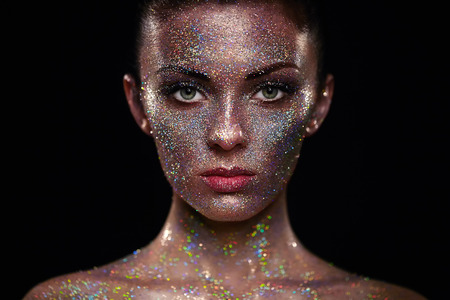 Portrait of beautiful woman with sparkles on her face. Girl with art make up in color light. Fashion model with colorful make-up Stok Fotoğraf - 64229087