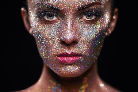 그녀의 얼굴에 반짝와 아름 다운 여자의 초상화. 예술을 가진 소녀 색상 빛을 확인합니다. 화려한 메이크업과 패션 모델