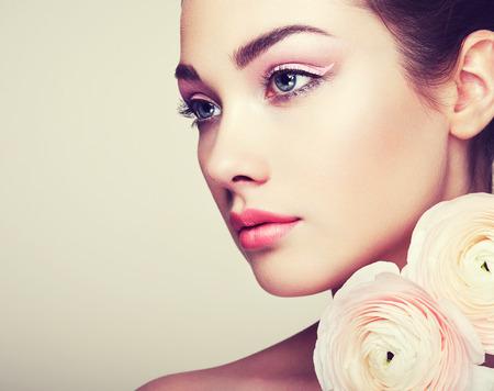 Ritratto di giovane e bella donna con fiori. Donna del Brunette con trucco di lusso. Pelle perfetta. Ciglia. ombretto Cosmetic