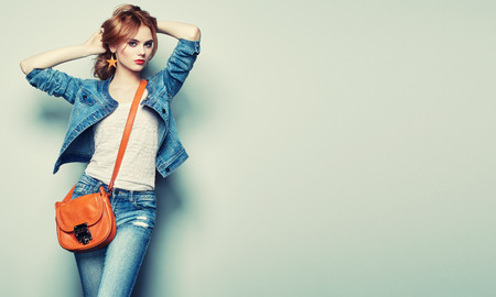 fashion bag: Fashion portrait of beautiful young woman with red hair. Girl in blouse and jeans. Jewelry and hairstyle. Girl with handbag