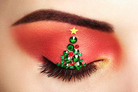 유행: 눈 소녀 화장 크리스마스 트리입니다. 겨울 크리스마스 메이크업. 뷰티 패션. 속눈썹. 화장품 아이 섀도우. 메이크업 세부 사항입니다. 크리 에이 티브