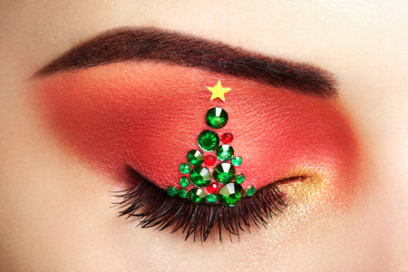 trend: Eye girl makeover christmas tree. Winter christmas makeup. Beauty fashion. Eyelashes. Cosmetic Eyeshadow. Makeup detail. Creative woman holiday make-up