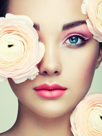 花を持つ美しい若い女性の肖像画。高級化粧品でブルネットの女性。完璧な肌。まつげ。化粧品アイシャドウ