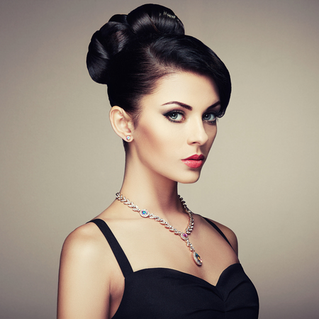 Fashion portret van jonge mooie vrouw met juwelen en elegante kapsel. Donkerbruin meisje. Perfecte make-up. Schoonheid stijl vrouw met diamant accessoires