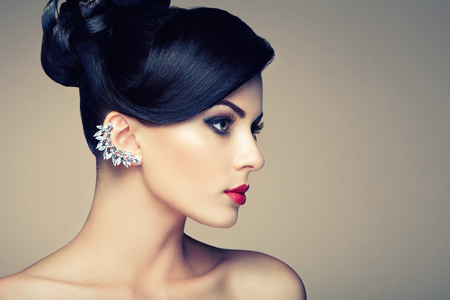 Fashion portrait of young beautiful woman with jewelry and elegant hairstyle. Brunette girl. Perfect make-up.  Beauty style woman with diamond accessories Banco de Imagens
