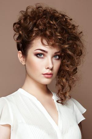 カーリーと光沢のある髪をブルネットの女性。ウェーブのかかった髪型に美しいモデルです。ファッション写真