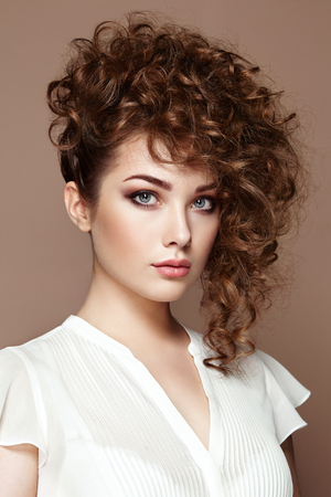 Brunette woman with curly and shiny hair. Beautiful model with wavy hairstyle. Fashion photo Stok Fotoğraf