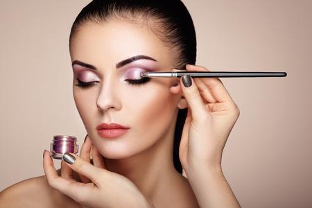 Make-up artiest toepassing oogschaduw. Mooie vrouw gezicht. Perfecte make-up. Make-up detail. meisje van de schoonheid met perfecte huid. Nagels en manicure Stockfoto - 65966218