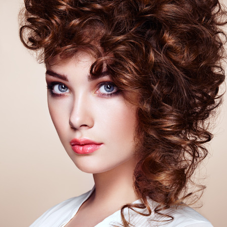forearms: Brunette woman with curly and shiny hair. Beautiful model with wavy hairstyle. Fashion photo Stock Photo