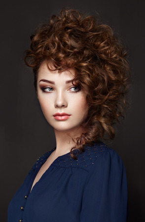 photo: Brunette woman with curly and shiny hair. Beautiful model with wavy hairstyle. Fashion photo Stock Photo