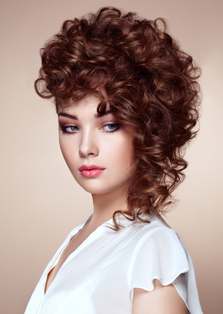 Brunette woman with curly and shiny hair. Beautiful model with wavy hairstyle. Fashion photo Stock Photo
