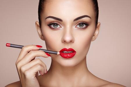 modelos posando: La mujer hermosa pinta los labios con lápiz labial. Cara de la mujer hermosa. detalle de maquillaje. Muchacha de la belleza con la piel perfecta. labios y uñas de color rojo manicura