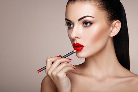 red lips: La mujer hermosa pinta los labios con lápiz labial. Cara de la mujer hermosa. detalle de maquillaje. Muchacha de la belleza con la piel perfecta. labios y uñas de color rojo manicura