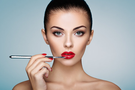Beautiful woman paints lips with lipstick. Beautiful woman face. Makeup detail. Beauty girl with perfect skin. Red lips and nails manicure Stock Photo