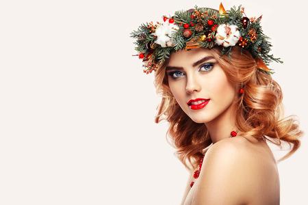 Portret van mooie jonge vrouw met kerst krans. Mooie Nieuwjaar en Christmas tree vakantie kapsel en make-up. Schoonheid meisje portret geïsoleerd op een witte achtergrond. Kleurrijke make-up en het haar