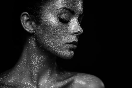 Portret van mooie vrouw met schittert op haar gezicht. Meisje met kunst make-up in kleur, licht. Fashion model met kleurrijke make-up. Zwart en wit