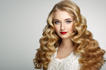 Piękne dziewczyny z długimi faliste i lśniące włosy. Blond kobieta z kręcone fryzura. Idealny makijaż. Fotografia mody