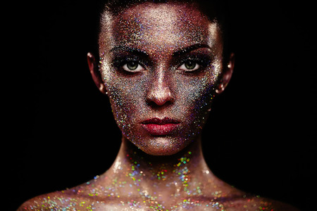 glitter makeup: Portrait of beautiful woman with sparkles on her face. Girl with art make up in color light. Fashion model with colorful make-up