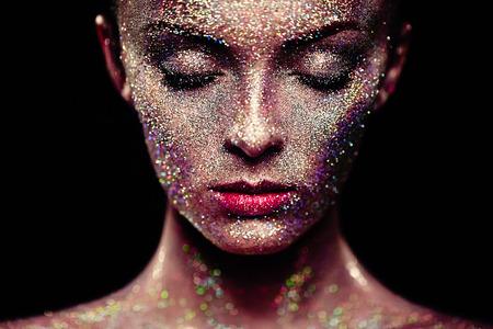 Portret van mooie vrouw met schittert op haar gezicht. Meisje met kunst make-up in kleur, licht. Fashion model met kleurrijke make-up Stockfoto