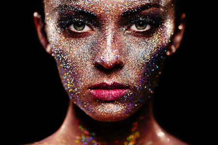 light to dark: Portrait of beautiful woman with sparkles on her face. Girl with art make up in color light. Fashion model with colorful make-up