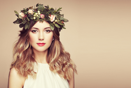Beautiful blonde woman with flower wreath on her head. Beauty girl with flowers hairstyle. Perfect makeup. Beauty fashion. Spring woman
