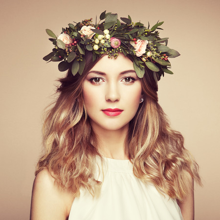 Beautiful blonde woman with flower wreath on her head. Beauty girl with flowers hairstyle. Perfect makeup. Beauty fashion. Spring woman Reklamní fotografie - 70401218