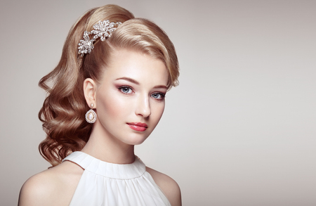 Fashion portrait of young beautiful woman with jewelry and elegant hairstyle. Blonde girl with long wavy hair. Perfect make-up.  Beauty style woman with diamond accessories Stock Photo
