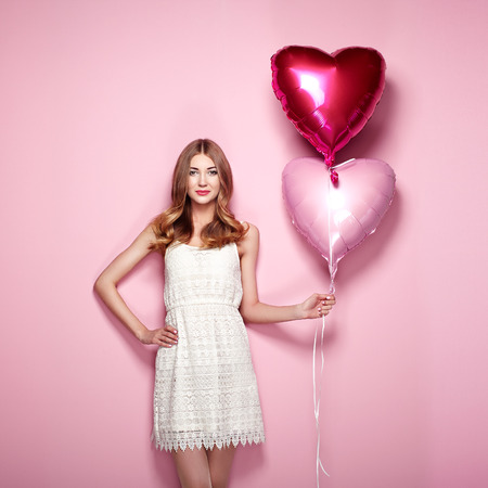 Beautiful young woman with heart shape air balloon on color background. Woman on Valentines Day. Symbol of love Stok Fotoğraf