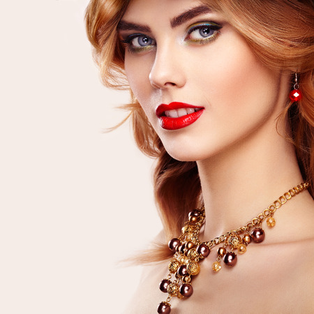 Beauty fashion model redhead girl portrait. Sexy young woman with perfect makeup and trendy golden accessories. Smiling cheerful girl in open white background. Fashion glamour female